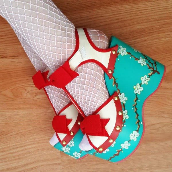 feet side by side on wooden floor wearing turquoise hand painted floral wedges with ivory patent uppers and red trim