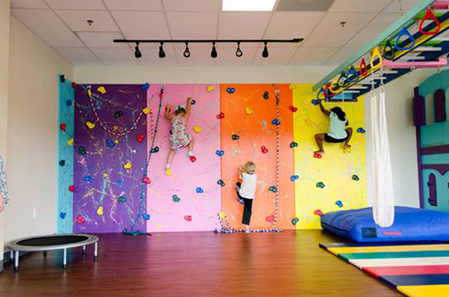 photo of sensory room at Mountain Ridge, with a rock climbing wall, trampoline, and other activity areas.