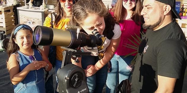 mujer mira a través de telescopio