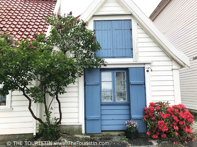 White wooden fishermens cottage with a blue door and shutters in Bergen in Norway.