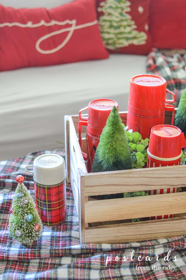 bottle brush trees and vintage red plaid thermoses in a wooden crate