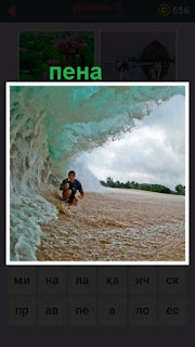 высокая волна с пеной под которой находится человек