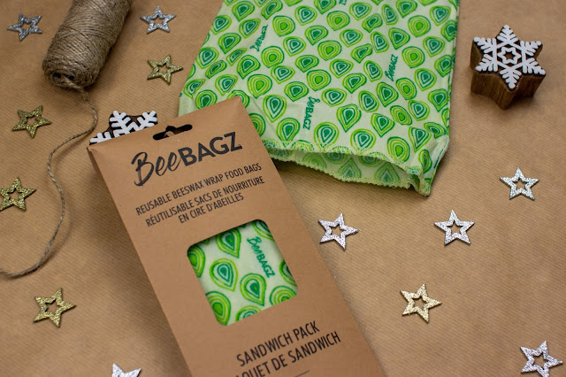 A sandwich bag made from reusable beeswax with a green pattern on next to a packet for the bag with a second one inside. The cardboard packet says BeeBagz Sandwich pack on it