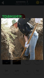 мужчина в шляпе роет траншею лопатой