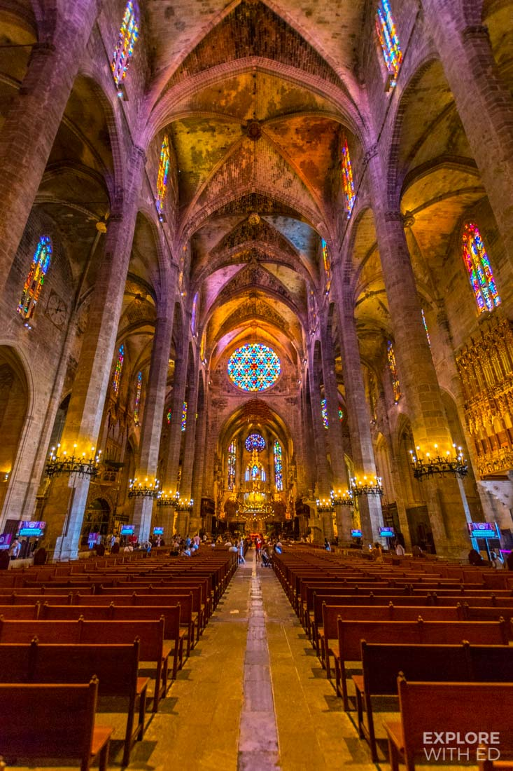 Inside Palma de Mallorca's stunning Cathedral where the sunlight fills the room in colours through the stained glass