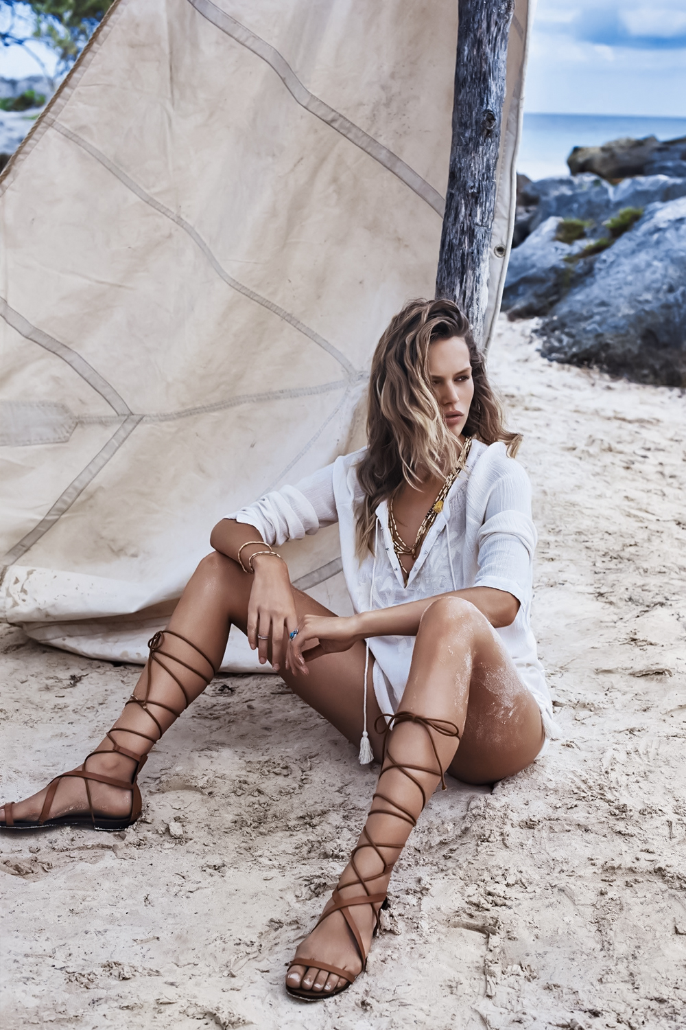woman in gladiator sandals in posing on a sandy beach