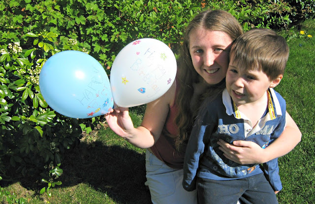 Two children in a garden, one holding a pair of balloons