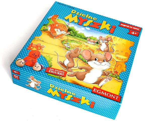 na zdjęciu pudełko od gry dzielne myszki, na niebieskim tle  mamy obrazek z uciekającymi myszkami, które goni kot