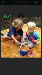 Двое детей играют в песочнице, собирая песок лопаткой в ведро
