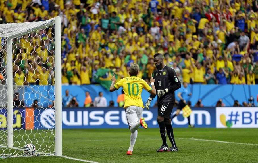 Brazil's Neymar runs past Cameroon's goalkeeper Charles Itandje after scoring his side's first goal during the group A World Cup soccer match between Cameroon and Brazil at the Estadio Nacional in Brasilia, Brazil, Monday, June 23, 2014.