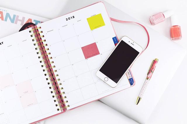 Celular iPhone sobre agenda feminina e uma caneta