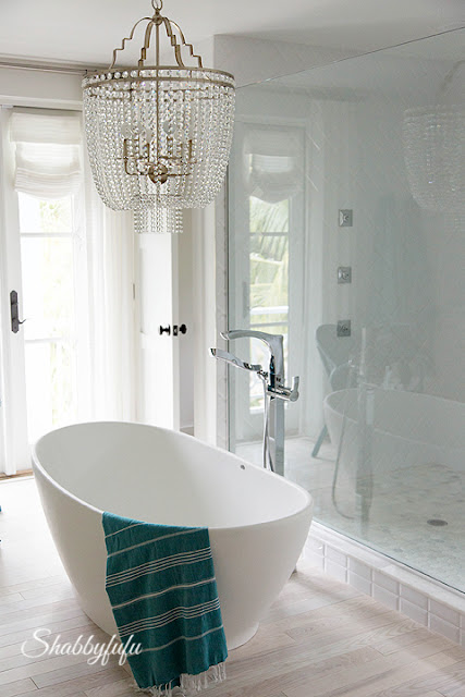 Master bathroom in the HGTV Dream Home 2016 - this bathroom is elegant with white and teal touches and a crystal chandelier.