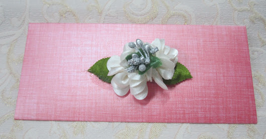 PINK ENVELOPE WITH WHITE FLOWER.