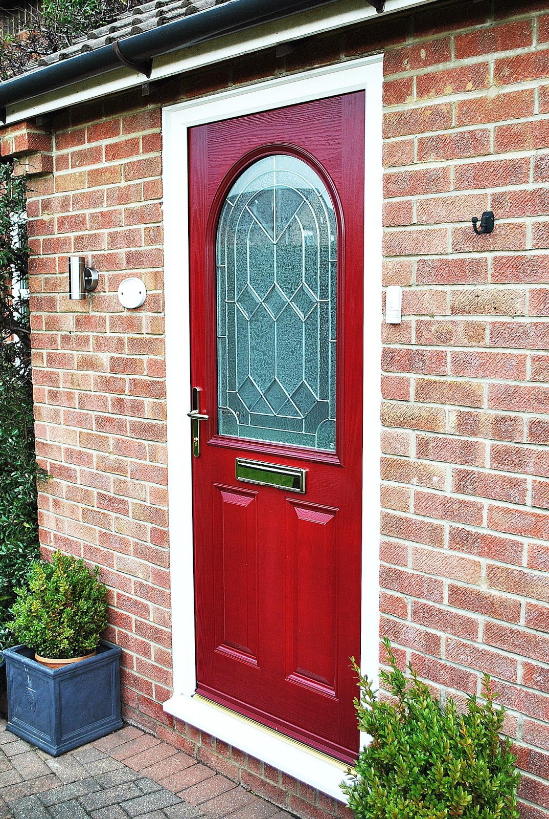 A Bold Statement Red Composite Front Door With Arched Glass Panel