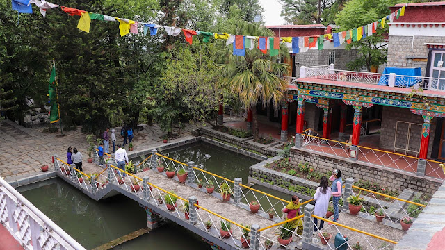 greenery, water flowing in the middle of the garden and prayer flags fluttering above your heads at Norbulingka