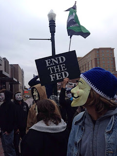 "Protesters wearing Guy Fawkes masks with ""End the Fed"" sign"
