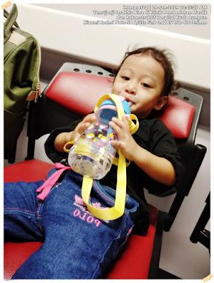 Gambar budak perempuan setahun sedang minum air atas kerusi menunggu giliran bertemu doktor di Hospital Kuala Lumpur.