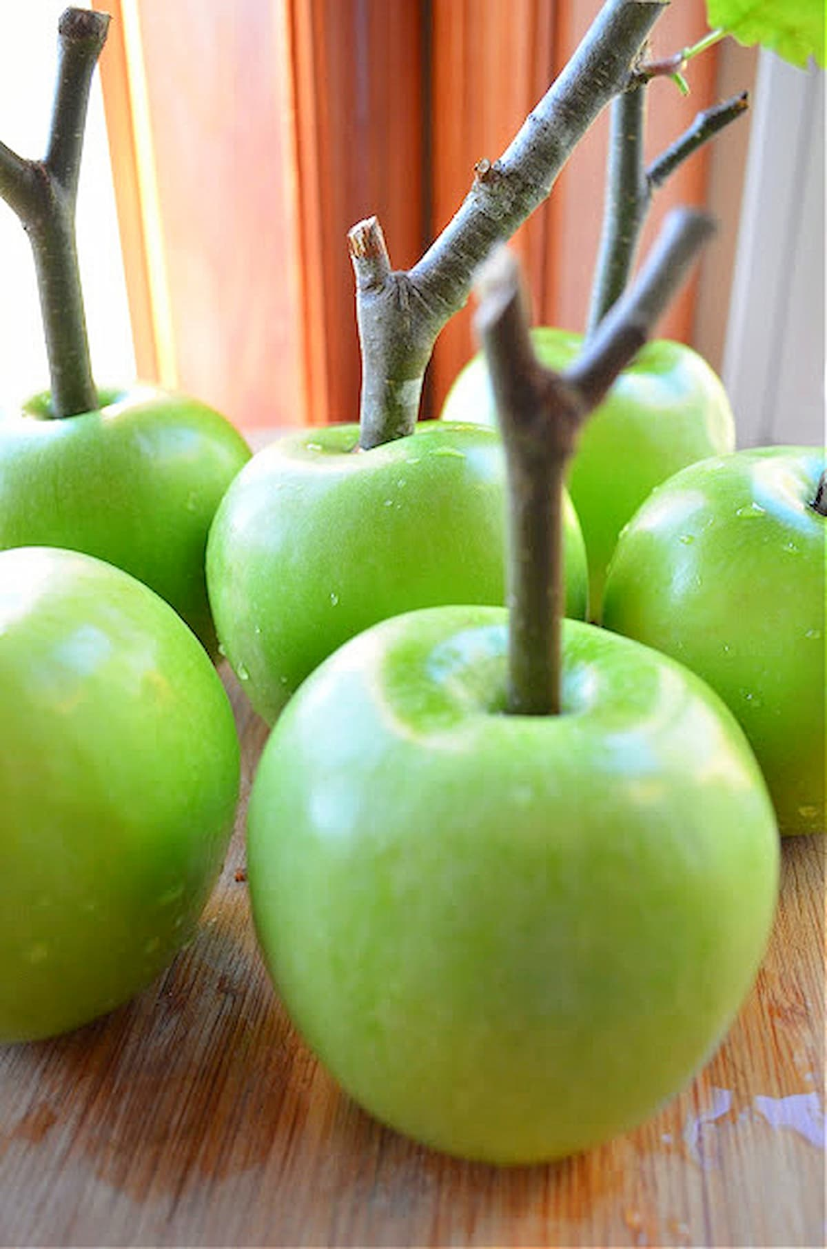 Apples with a Apple Twig in the center on a wooden cutting board.
