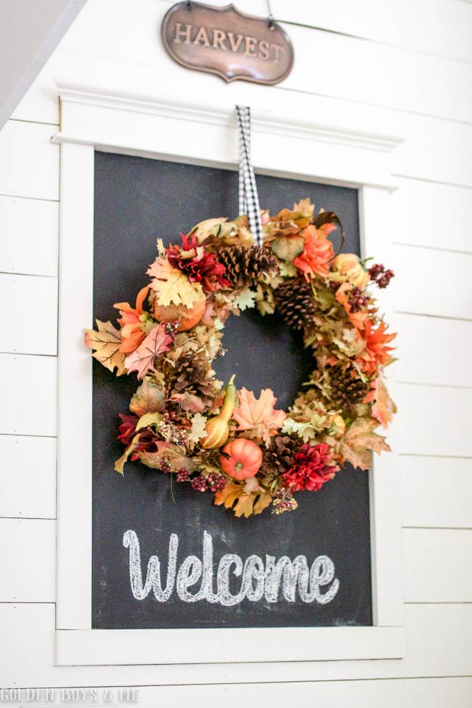 Colorful fall wreath displayed on chalkboard for fall decor in entryway - www.goldenboysandme.com
