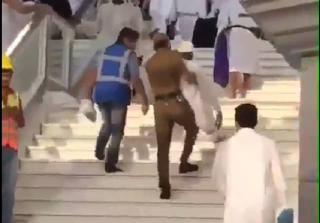 A SECURITY OFFICER CARRIES ELDERLY PILGRIM UP THE STAIRS IN MAKKAH