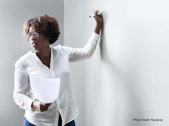black woman educator whiteboard instructions Credit Rawpixel