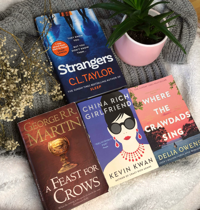 Four books face up in a triangle: Strangers, A Feast for Crows, China Rich Girlfriend, and Where the Crawdads SIng