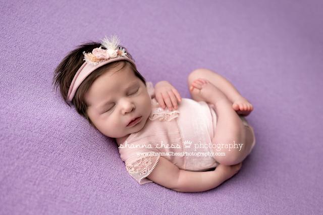 Newborn photo studio Eugene Oregon, baby girl asleep on purple beanbag