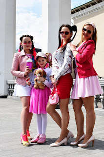 Три девушки и девочка в розовом возле колонн