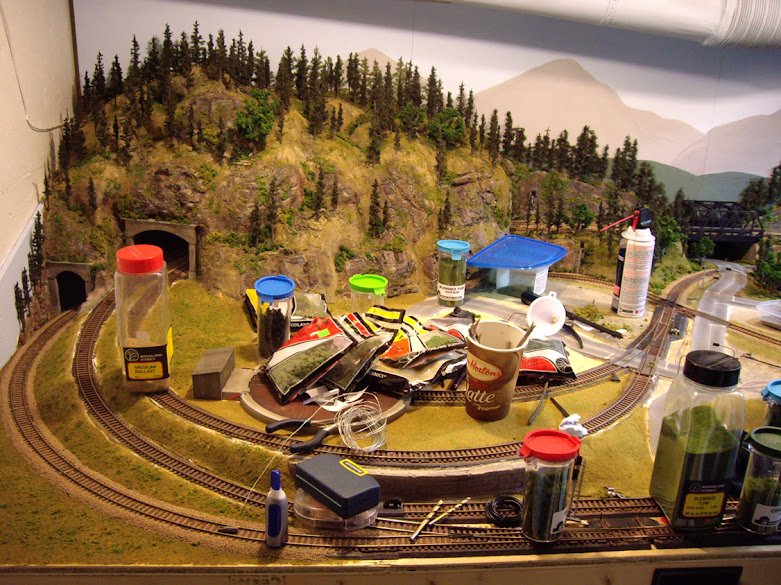 A partially complete HO model railroad layout cluttered with various scenery construction materials