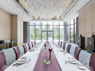 Source: Langham Hospitality Group. Perspective view of a long dining table.