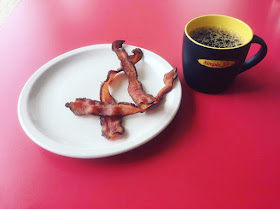 A cup of River Road Coffee and a side of bacon at Simple Joe