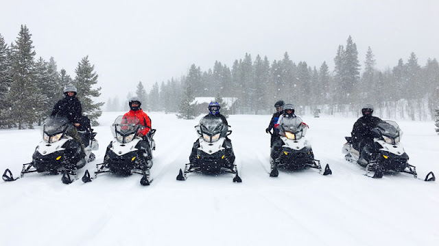 five snowmobile riders lined up as snow falls