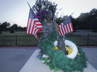 a bronze sculpture of a dog and John Douangdara, a dog handler for the Navy SEALS who died in Afghanistan in a helicopter crash, is covered in flowers and American flags