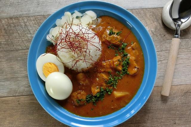 皿にご飯を盛り付け、ブラックペッパーを振るいます。カレーを注ぎ、刻みらっきょう、ゆで卵、刻みパセリを散らして仕上げに細切り唐辛子をのせて完成です。