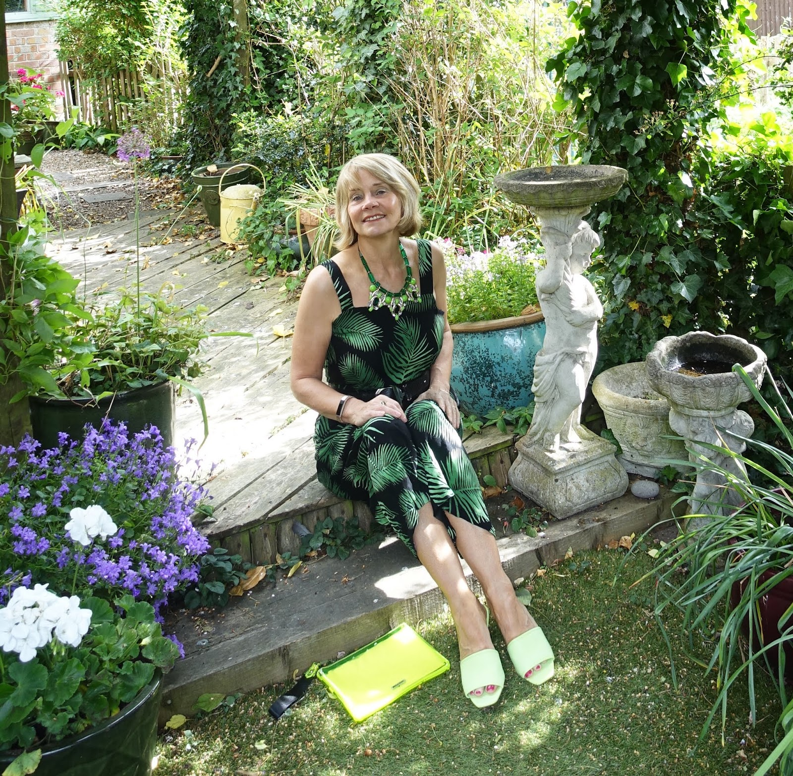 Seated in the garden is This Mutton bloggeer Gail Hanlon in green and black palm print jumpsuit for the Style Not Age Challenge: jungle prints