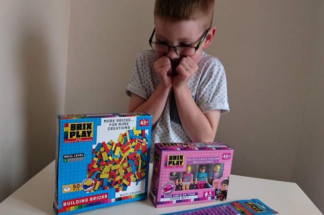 Blonde haired boy wearing glasses and white short sleeved top with blue + signs looking very excited with his hands up at his face. The white table in the front of the picture has two boxes of Brix Play blocks and people along with two sticky back purple Brix Play strips