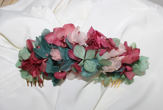 Tocado con peinetas de flores de hortensia preservadas en verde y buganvilla