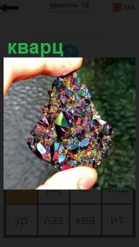 В своих руках человек показывает цветной кварц, который переливается на свету