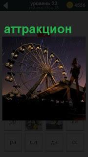 В свете вечернего неба вращается колесо обозрения, Аттракцион подсвечивается с низу огнями прожекторов