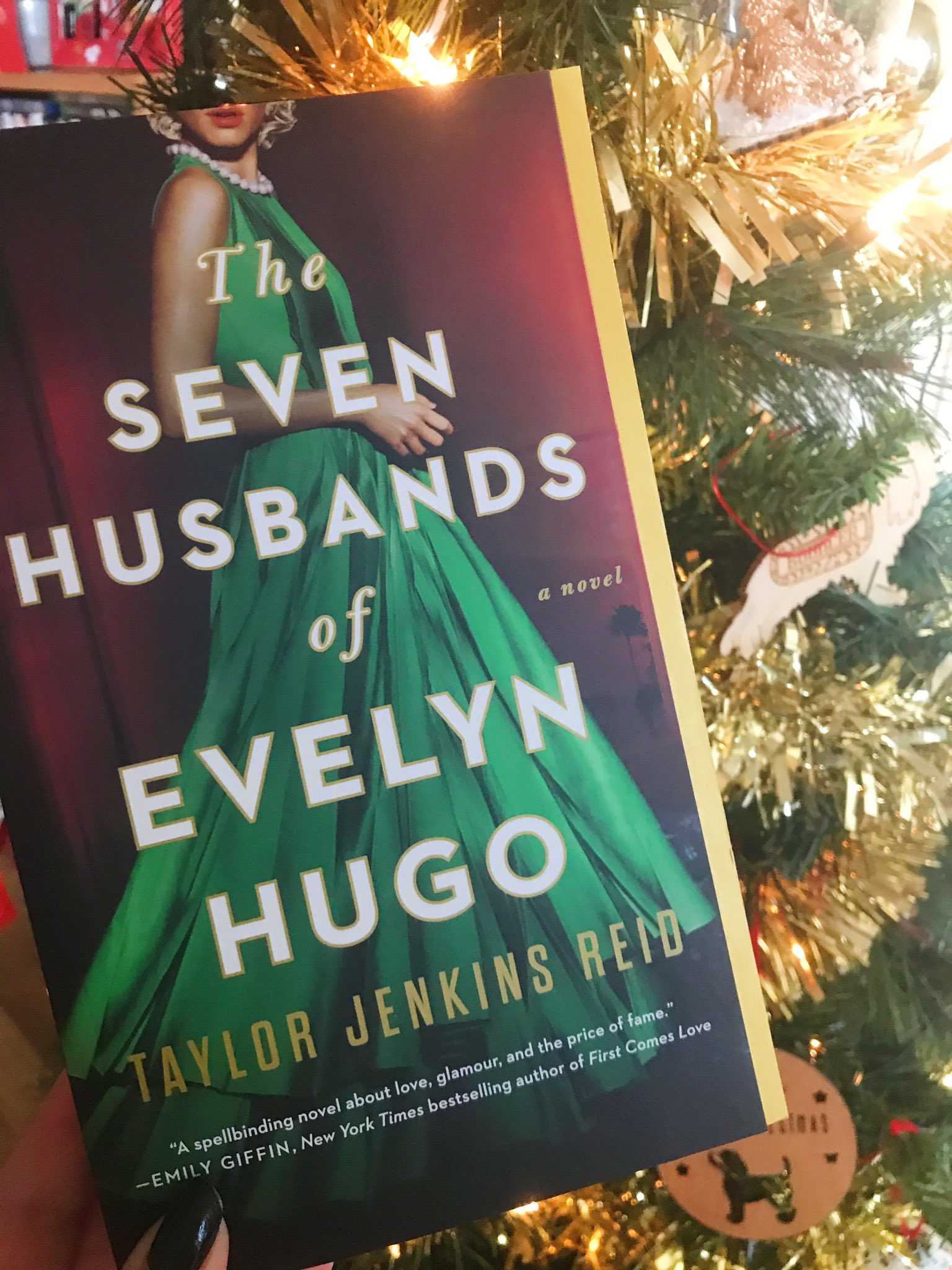 The Seven Husbands of Evelyn Hugo by Taylor Jenkins Reid book held up in front of the Christmas tree