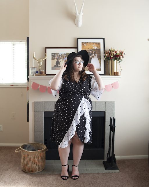 An outfit consisting of a wide brim black hat, white on black polka dot with black on white polka dot short flounce sleeves and ruffles wrap dress and black ankle strap heels.