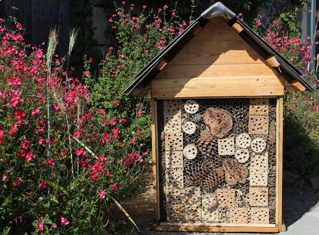 Large insect hotel to cover and camouflage a utilities box