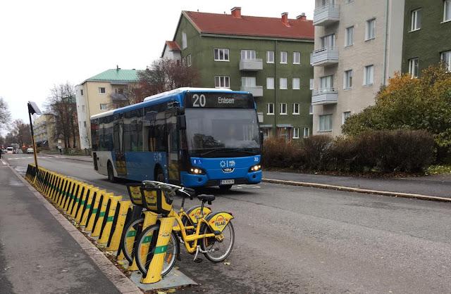 Linja 20 bussi, kerrostaloja taustalla.