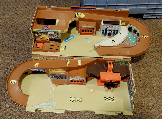 A vintage hot wheels play set with city buildings. Two levels and folds up for storage.