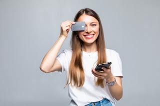 mulher jovem segurando um cartão na frente do olho e celular na outra mão