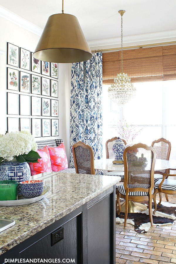 botanical gallery wall, blue and white drapes, round tulip table, vintage cane dining chairs