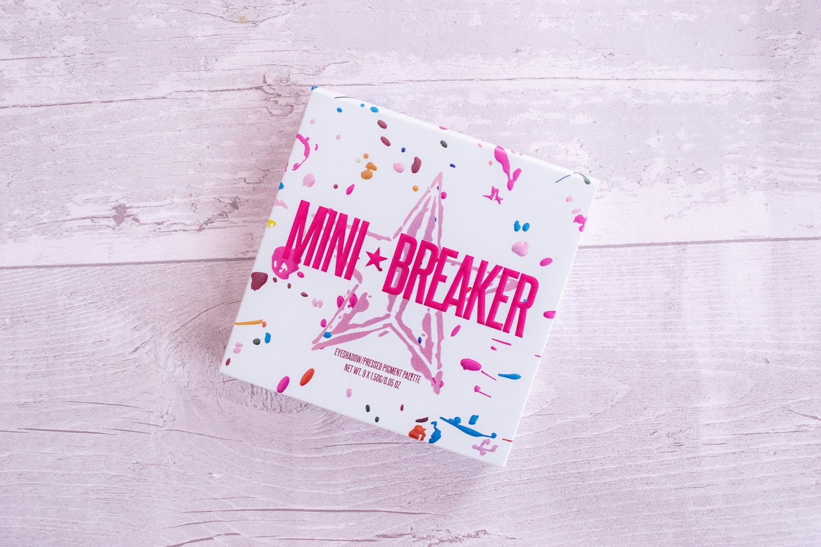A close up of the Jeffree Star Mini Breaker palette. The palette is white with blue and pink splats over and the Jeffree Star logo in pink under the words Mini Breaker.