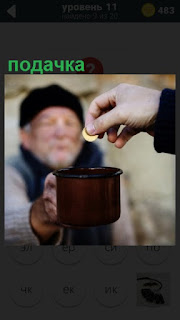 подачка нищему денег в протянутую чашку на улице