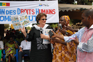 Tostan Executive Director, Molly Melching (left), presents the human rights booklet to the community, project partners, and local government officials.