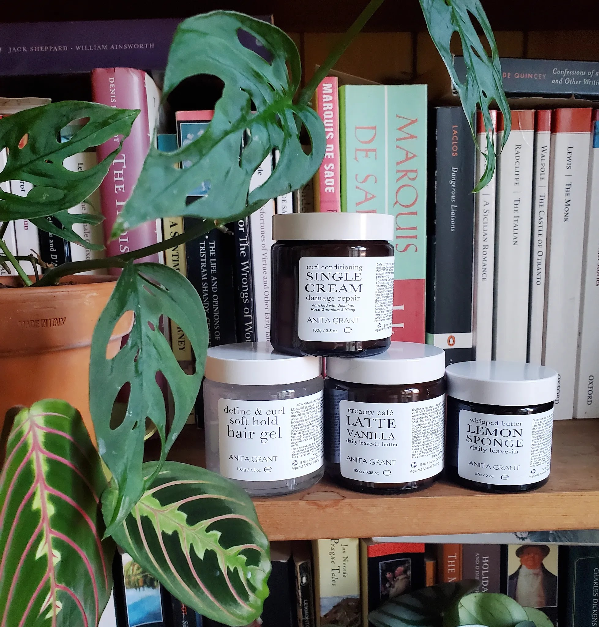 four Anita Grant natural haircare products stacked together on a bookshelf surrounded by leafy plants
